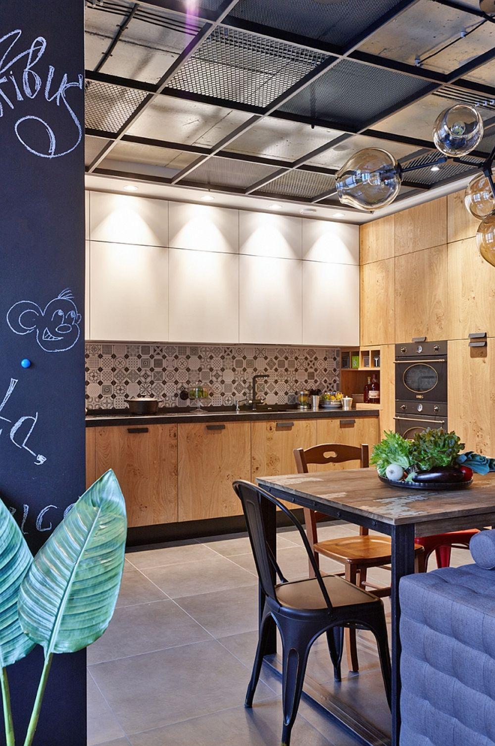 În lateralul bucătăriei sunt încastrate electrocasnicele mai mari - cuptor, cuptor cu microunde, frigider, alături de spații de depozitare. Totul însă este tratat similar unei placări cu lemn, ceea ce adăugă o notă binevenită de căldură spațiului creionat cu tușe de negru.
