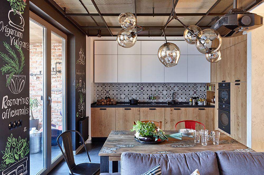Spațiul bucătăriei este compact gândit cu electrocasnice încorporate. Corpurile suspendate sunt până în plafon de nuanță albă pentru a amplifica senzația de luminozitate. Faianța cu model mărunt alb-negru este din același registru cu placarea din hol și se leagă frumos de baltul negru al mobilierului.