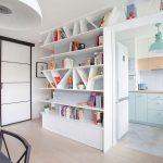 Biblioteca încadrează golul  accesului în bucătărie, formând o intrare mai interesantă în spațiul destinat activităților culinare.