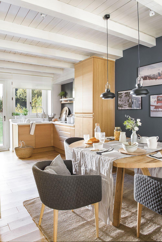 Mobila de bucătărie a fost păstrată așa cum era înainte, dar ea se simte altfel cu finisajele schimbate, respectiv peretele din zonă vopsit în gri colorat și plafoanele albe. S-a creat un contrast cromatic cu fețele din lemn, care acum sunt puse în evidență. În lo de faianță, pereteledin zona sensibilă este protejat cu placare similară blatului. Fiind deschisă către restul casei, bucătăria beneficiază acum de aceeași pardoseală din lemn ca și în restul zonei de zi.