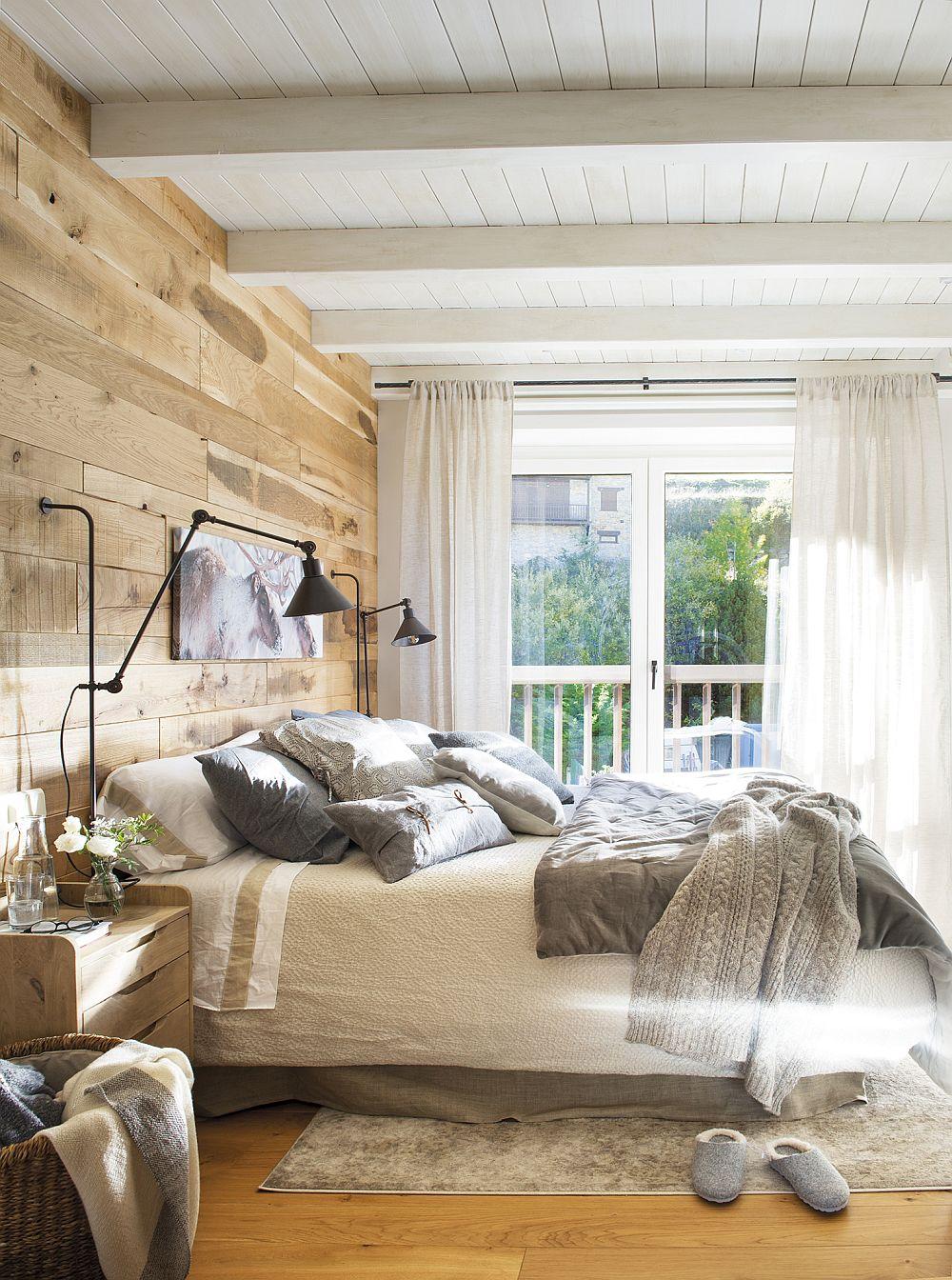 Dormitorul matrimonial vorbește prin amenajare de destinația de vacanță a casei. Peretele din spatele patului a fost îmbrăcat cu lemn recupaerat dispus pe orizonatală pentru a da senzația de lățime a camerei. Peretele acesta este pus în valoare prin contrast cu plafonul alb, dar și cu zona de fereastră încadrată de draperii albe. De asemenea, contează mult și faptul că patul este îmbrăcat pe o suprafață mare cu o cuvertură deschisă la culoare. O cameră care inspiră relaxare și parcă te invită la lectură.