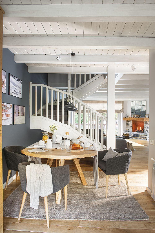 Locul de luat masa era inițial mai aproape de fereastra din living, însă după reamenajare, designerii au repoziționat locul sufrageriei între bucătărie și scara interioară. Astfel s-a exploatat un spațiu care înainte nu era deloc folosit. Și aici s-a mers pe contrastul de lemn cu griuri și alb. Covorul adaugă o notă familiară, la fel ca și tapițeria textilă a scaunelor. Masa din lemn masiv realizată pe comandă după schițele designerilor este elementul cald din acest colț al casei. De remarcat cât de mult contează albul pentru senzația de luminozitate, respectiv plafonul, scara interioară și accentele decorative deschise.