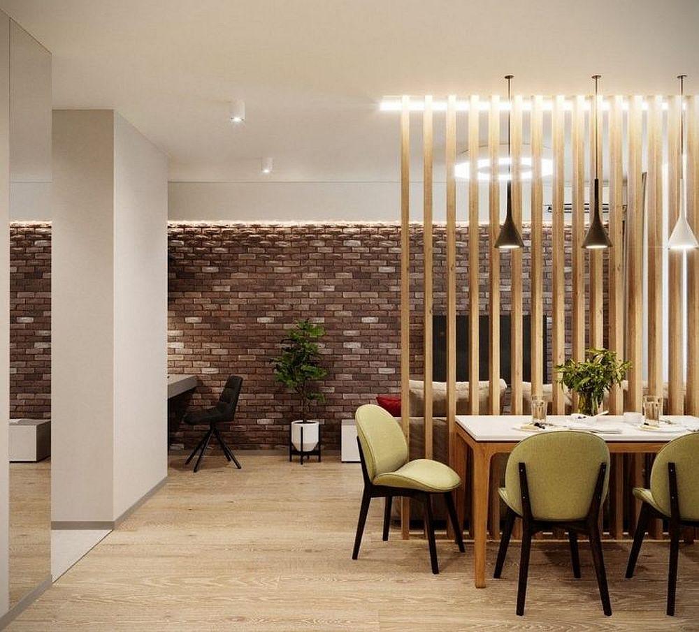 Zona locului de luat masa și implicit a bucătăriei este parțial separată de restul prin intermediul riflajelor din lemn. Acestea ajută și la fixarea canapelei, un model extensibil, care devine loc de dormit pe timpul serii.