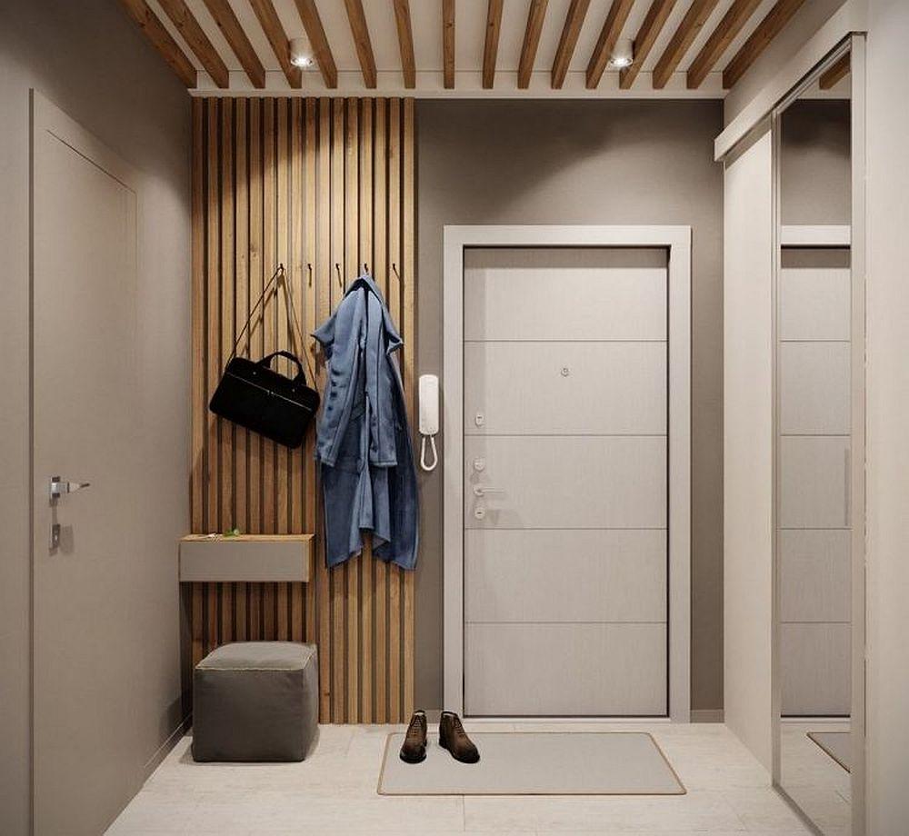 Lângă ușa de la intrarea în casă a fost configurat un cuier simplu cu riflaje. În stânga este ușa de la baie vopsită în aceeași nuanță cu a peretelui, iar în dreapta este dressingul separat cu o ușă culisantă placată cu oglindă.