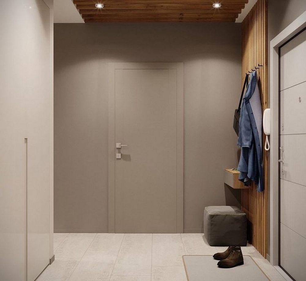 Accesul la baie se poate ghici după clanța ușii, altfel ar fi fost greu de identificat ușa pentru că este camuflată cromatic în holul de la intrare. Acest perete cu ușă se vede de la interiorul camerei, ca atare designerii nu au dorit să atragă atenția asupra ei.