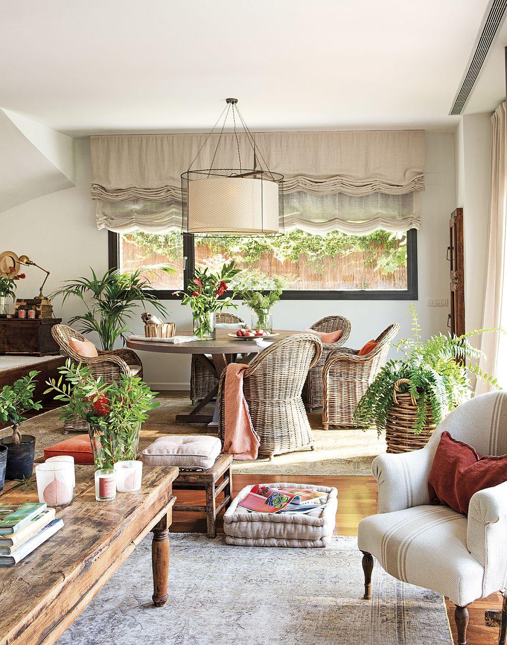 Zona de conversație din living comunică deschis cu sufrageria. Prezența plantelor contează mult în decorul rustic vizat.