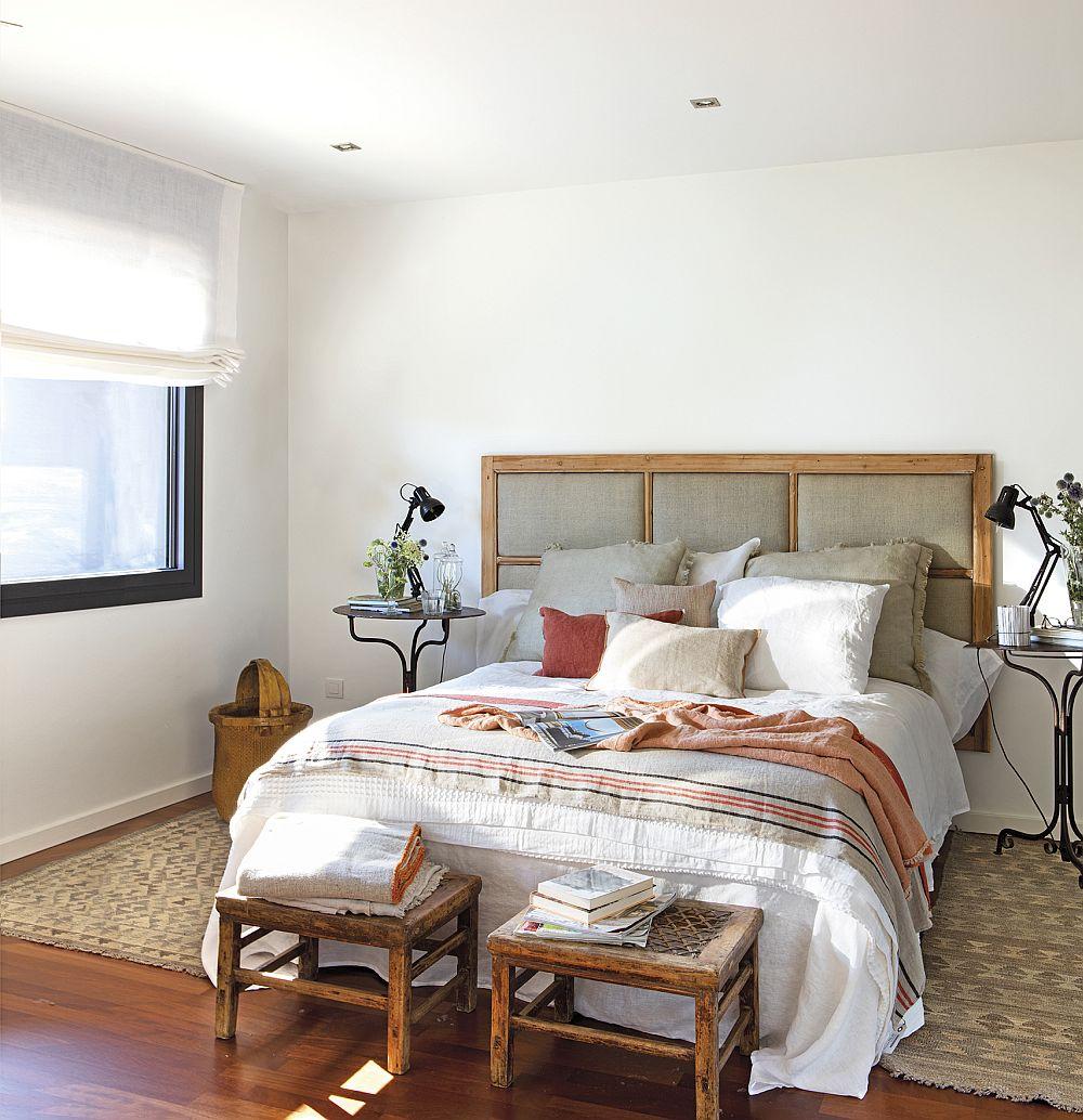 Dormitorul matrimonial este simplu, iar rusticul este sugerat prin tăblia tapițată montată pe perete, prin taburele din fața patului, de măsuțele metalice pe post de noptiere și evident prin țesăturile de aici cu motive geometrice și materiale naturale.