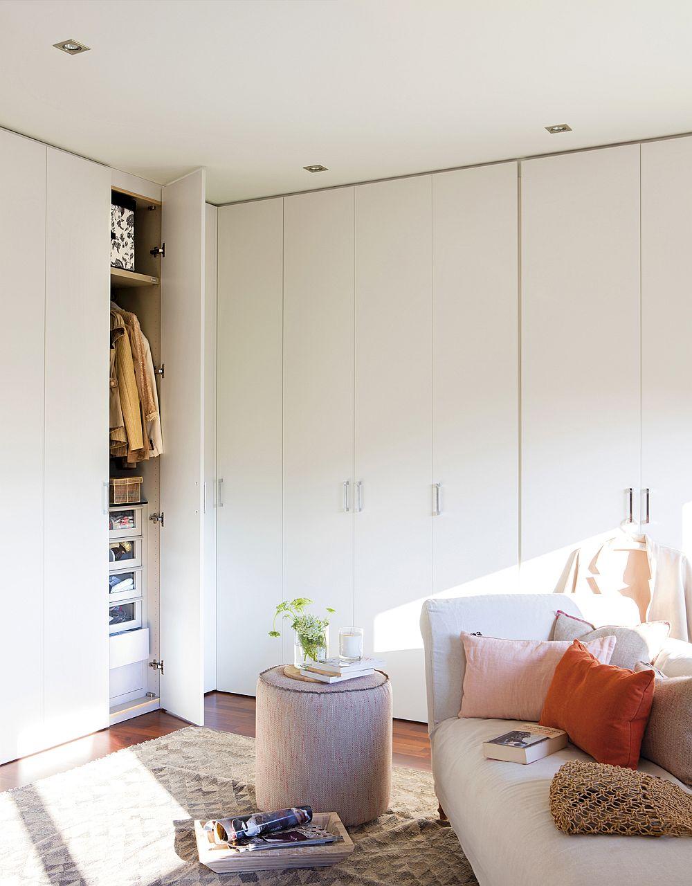 Dulapurile simple, albe se camuflează bine ăn ansamblul camerei finisată cu vopsea lavabilă albă. O sofa cu tapițerie textilă, un taburete rotund, un covor cu motive geometrice creionează o zonă altfel austeră din dormitor.