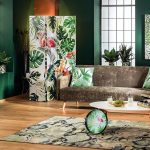 Canapea maro, parchet auriu? Cu tonuri de verde poți crea un contrast sofisticat, iar cu decorațiuni cu imprimeuri vegetale aduci și mai multă varietate în ambient. În foto colecția aJungle de la Kika.