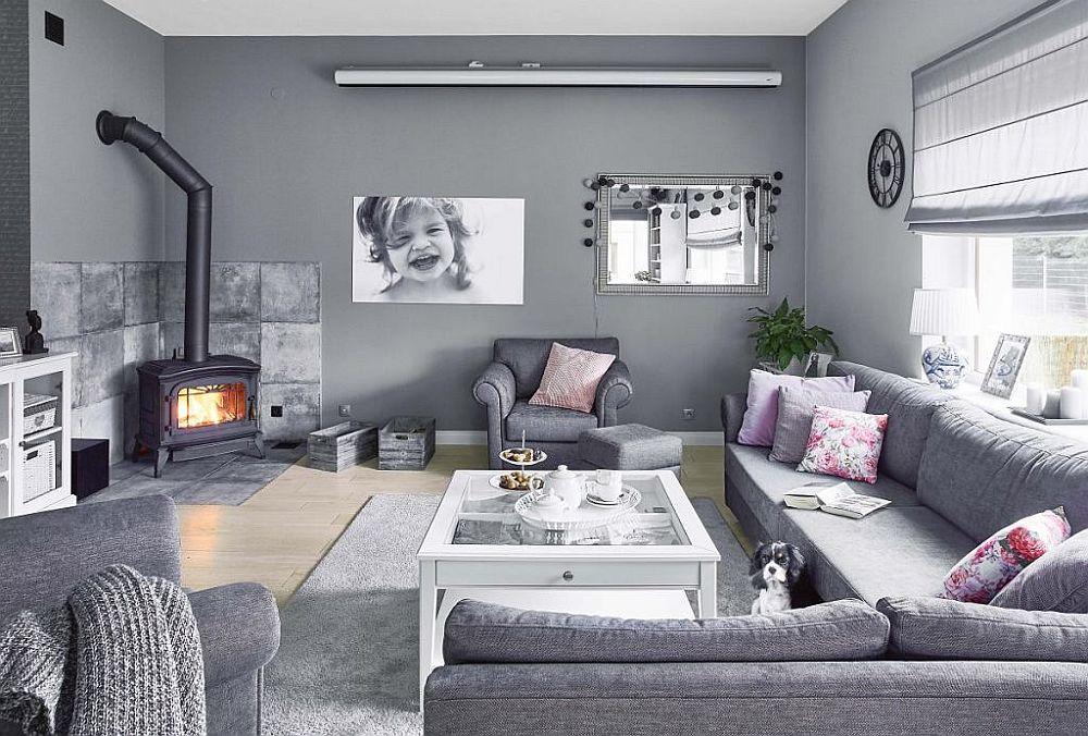 Livingul este simplu amenajat, iar griurile domnină ambientul, de la nuanța pereților la tapițeria canapelei și fotoliilor. Ca atare încăperea pare mai aerisită și mai simplă, griurile punând în evidență fereastra generoasă de aici. În locul unui șemineu s-a optat pentru o sobă de tip godin, iar spațiul din jurul ei este protejat cu plăci ceramice.