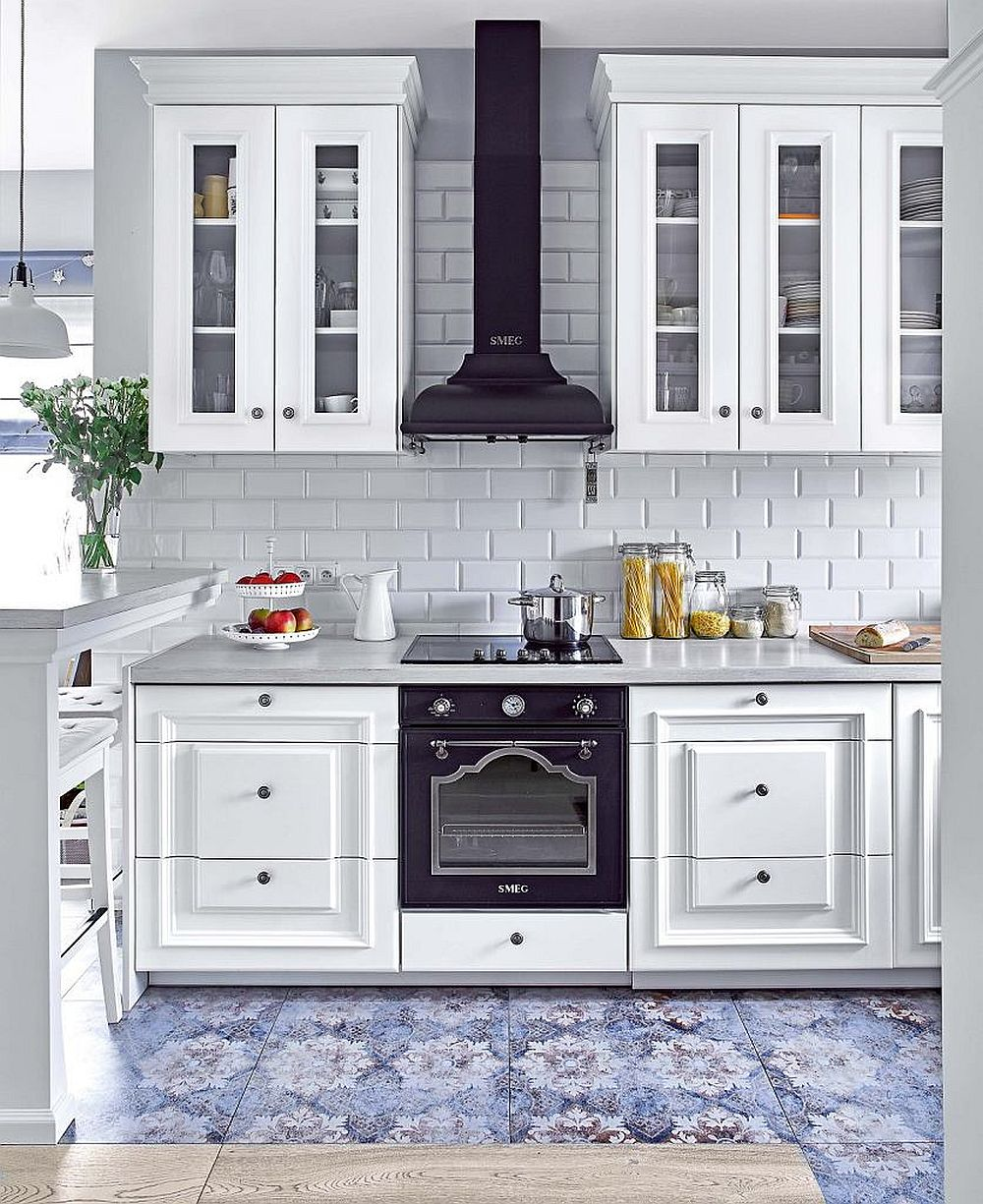 Bucătăria are aerul provensal pe care și-l dorea proprietara prin designul mobilierului, nu neapărat prin culoarea lui. Fronturile cu frezări, mânerele alese au impus și alegerea unor electrocasnice cu design clasic. Designerul a propus ca acestea să fie negre pentru a da senzația de simetrie într-o bucătărie organizată în formă de U. De asemenea, hota fiind decorativă, peretele a fost placat și în spatele ei. Pe pardoseală, plăcile ceramice de la Villero & Boch dau impresia de covor.