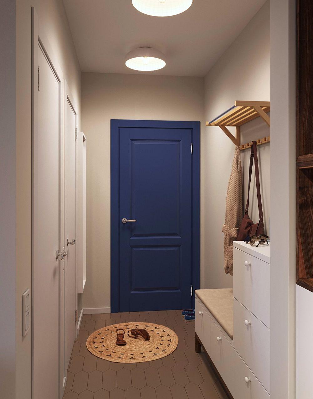 Pentru că e deschis către living, holul de la intrare (3,3 mp) a fost tratat cât mai atent cu putință. Un cuier minimal există aici, ca și o banchetă cu sertare și un pantofar minimal. Ușa de la intrare este vopsită în albastru, o pată de culoare binevenită într-un spațiu mic unde ușile interioare albe s-au dorit a fi camuflate în ansamblul pereților albi.