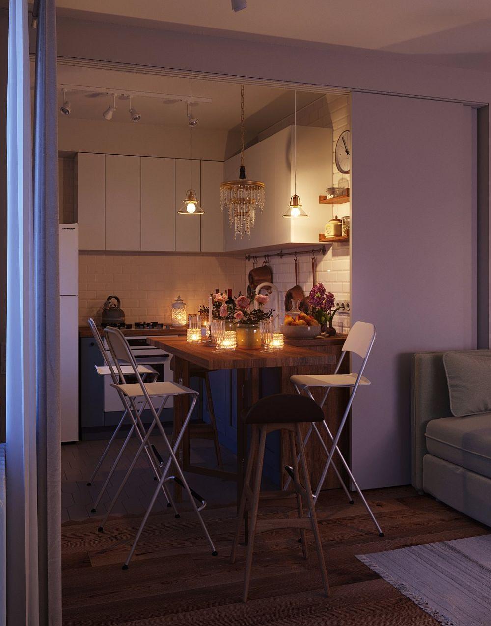 Pentru ca locul de luat masa să fie mai generos, arhitecții au prevăzut ca laterala blatului din bucătărie să poată fi rabatată către cameră pentru a forma o masă la care să poată sta patru persoane.