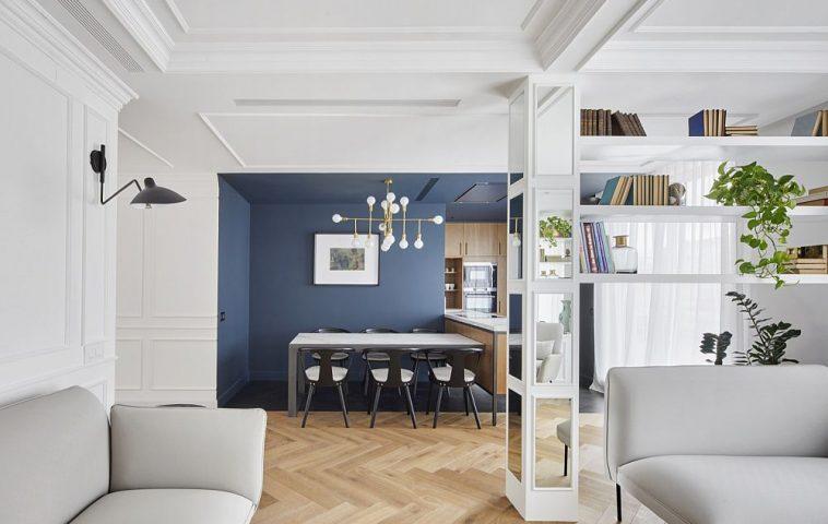 Stâlpul de rezistență dezgolit după desființarea peretelui dintre bucătărie și living a fost folosit pentru crearea unui loc de bibliotecă.