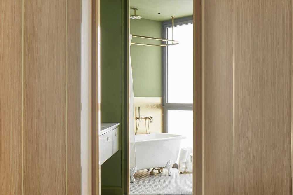 Baia retrasă, cu peretele poziționat oblic este conturată într-un contrast elegant de verde și auriu, dar în relație cu dormitorul placat cu panouri din lemn.