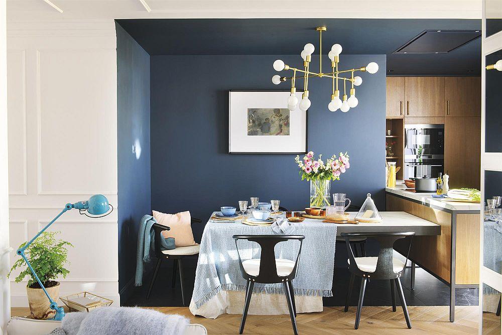 Pentru a amplifica senzația de lumină, designerul a prevăzut ca în sufragerie și bucătărie să fie create alte contraste. Pe fundalul nuanței de albastru ce îmbracă și pereții a amplasat un corp de iluminat cu suport aurit, care prin strălucirea lui dă senzația de lumină și lux. Apoi, mobila de bucătărie este cu textură din lemn în nuanța mierii, ceea ce contribuie la senzația de căldură, atenuând răceala albastrului și amplificând lumina naturală. Decorațiunile, cum ar fi tabloul cu parspartuu alb sau detaliile negre de la nivelul scaunelor și ale structurii mobilierului vin să creioneze alura grafică a volumelor prezente în acest spațiu.