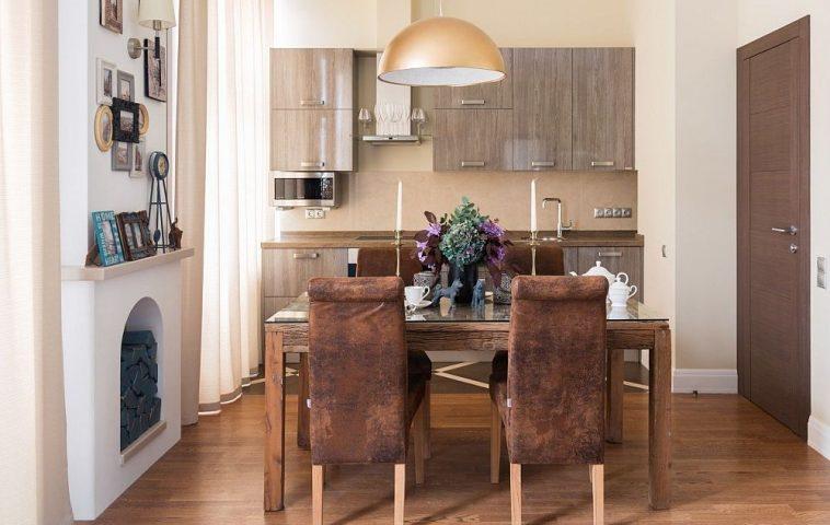 Zona de bucătărie este estompată de prezența mesei cu scaune pentru care designerii au prevăzut un ambient primitor care să se vadă frumos încă de la intrarea în casă.