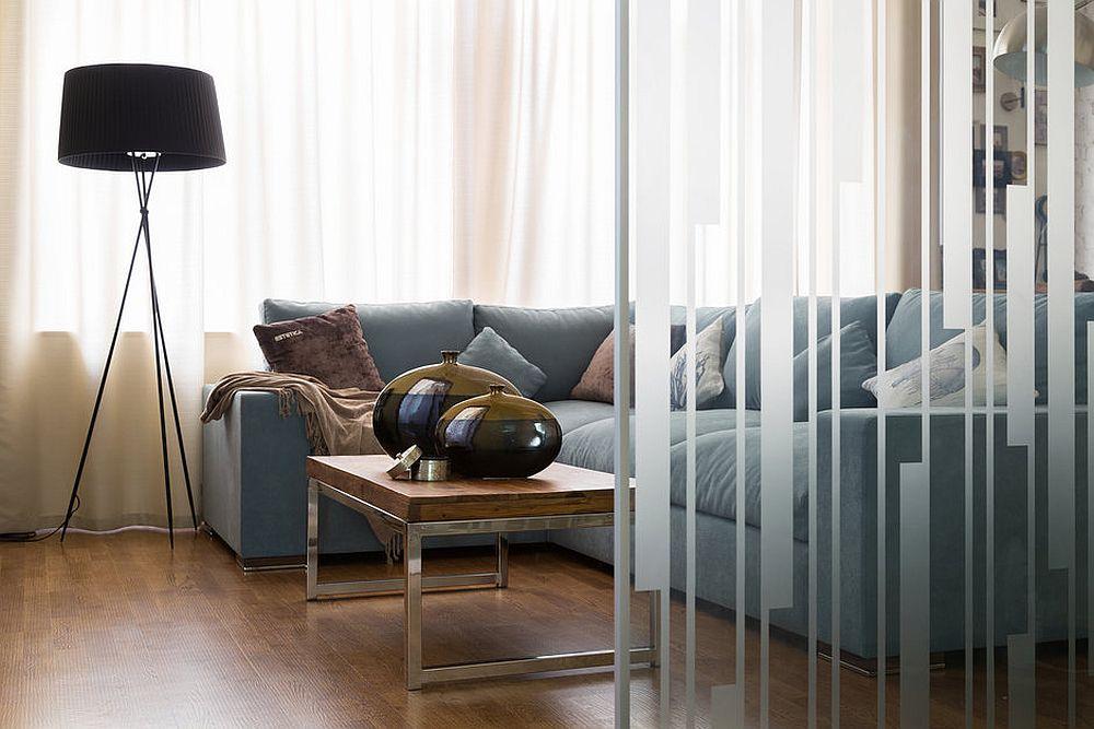 Canapeaua este poziționată pe centrul spațiului și în fața ferestrelor, dar faptul că zona de geamuri este lăsată liberă face ca livingul să se simtă mai amplu și mai aerisit.