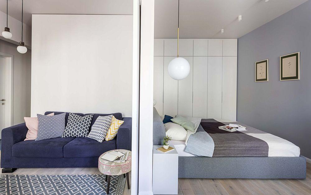 Chiar dacă în planuri dferite, spațiile de dpozitare sunt situate pe aceeași latură în locuintă. În spatele canapelei, după perete există un dulap generos, iar pe un întreg perete din dormitor un alt dulap îmbracă similar unei placări toată zona.