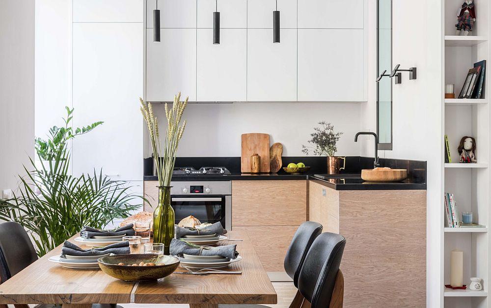 Legătura dintre bucătărie și zona de living s-a făcut frumos prin intermediul texturilor de lemn. Corpurile suspendate și frigiderul încorporat sunt cu fronturi de mobilă albe pentru a nu încărca spațiul, iar zona de lucru din bucătărie are corpuri cu texturi din lemn. Practic, la nivelul de jos masa de sufragerie continuă texturile din lemn prezente în bucătărie.