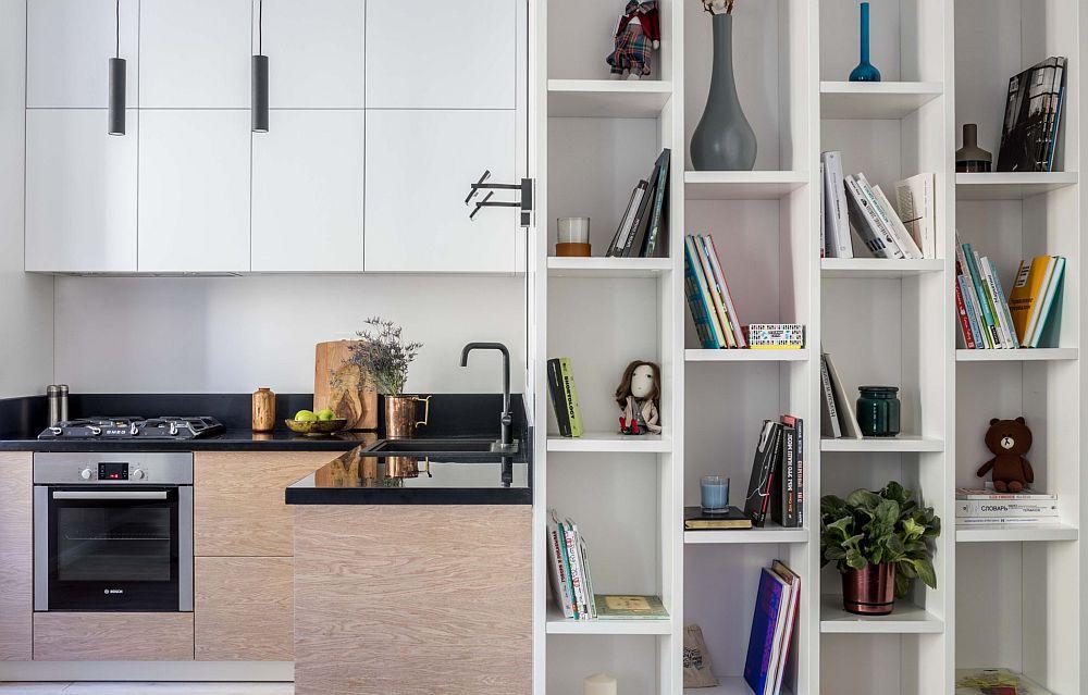 Între bucătărie și ușa de acces în baie, designerii au gândit o bibliotecă îngustă. Un extraloc de depoziatre într-o zonă de circulație, care însă leagă frumos funcțiunile din casă și maschează de la intrarea în casă prezența bucătăriei.