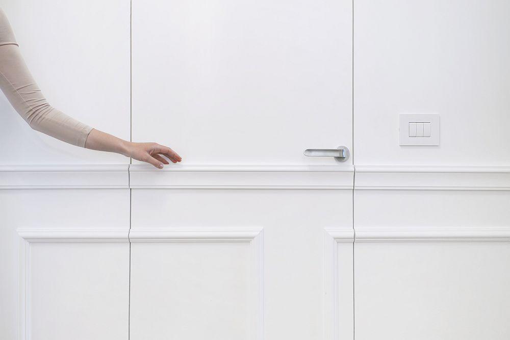 Arhitectele au prevăzut ca toată suprafața vizibilă dinspre living către hol să fie tratată cu tuțe clasice, iar desenul profilelor ce decorează pereții să fie continuat și pe foile de ușă. Profilele decorative pentru pereți, plintele și cornișele au fost achiziționate pe comandă de la Elegance Decor, iar ușile realizate pe comandă la White Design.