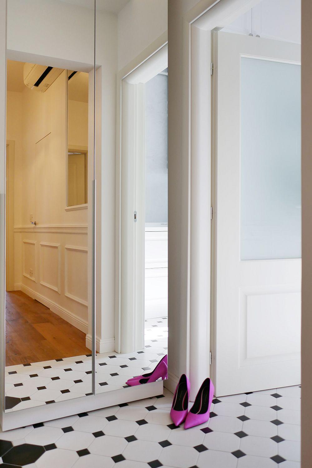 Pentru continuitate, plăcile ceramice octogromale din holul de la intrare se continuă și în bucătărie. În oglinda dulapului cu rol de cuier din holul de la intrare se poate observa al doilea hol care face legătura către celelalte camere ale locuinței.