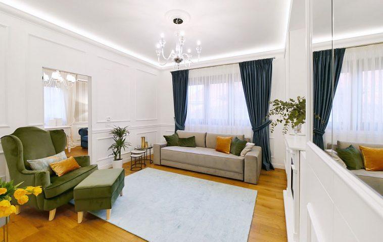 Livingul este o încăpere primitoare, cu accente clasice, dar luminos și aerisit fără a fi încărcat de mobilier. Canapeaua, fotoliul și taburetul toate tapițate au fost realizate pe comandă la firma EverArt, covorul este d ela Mobexpert, iar draperiile și perdelele realizate pe comandă la firma Emerald 2000.
