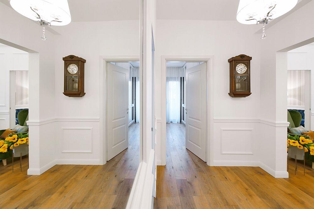 Din holul de legătură se poate observa accesul în living, care este deschis, golul fiind conturat simplu, cu linii clare. Arhitectele au prevăzut folosirea din plin a nuanței de alb pentru mai multă luminozitate și eleganță. S-au folosit vopseluri de la Caparol din gama premium.