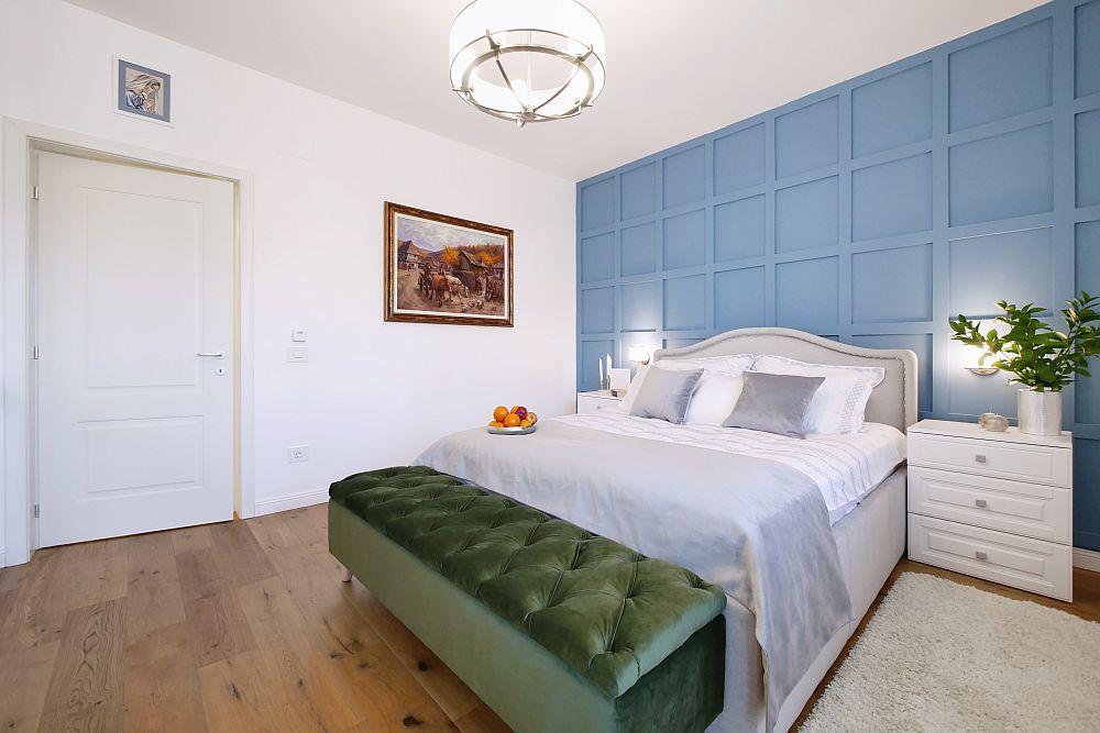În dormitor a fost poziționat tabloul proprietarilor, care pentru ei este o amintire dragă. Este pus în lateral pentru a putea fi văzut și din pat. În spatele tăbliei patului peretele este decorat cu profile din durolimer de la Elegance Decor și totul este vopsit apoi cu vopsea Eggshell de la Benjamin Moore.