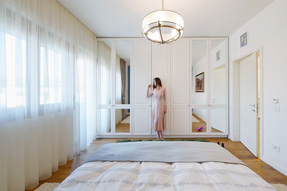 Pentru ca dulapul din dormitor să nu devină în niciun fel apăsător, arhitectele au prevăzut oglinzi poziționate pe linia noptierelor. Astfel spațiul pare mult mai mare și mai adânc.