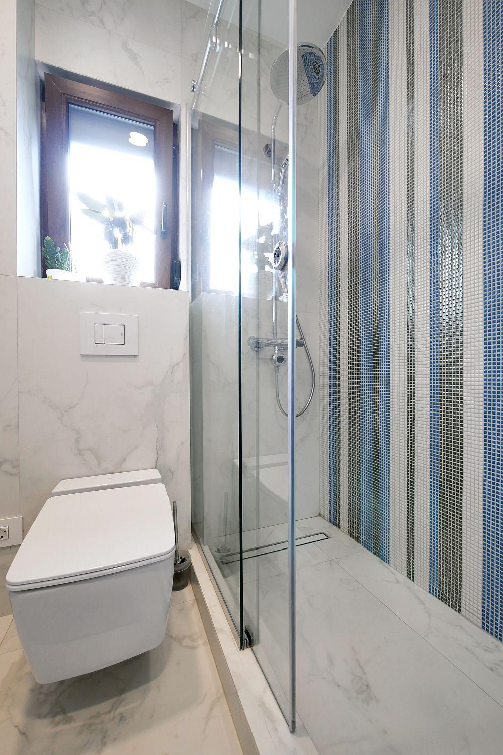Baia are o suprafață mică și atipică, cu multe colțuri și a trebuit integral refăcută. În locul căzii s-a optat pentru o cabină de duș construită închisă cu panouri de sticlă realizate pe comandă la firma Decoflex. Obiectele sanitare au fost achiziționate de la Delta Studio.