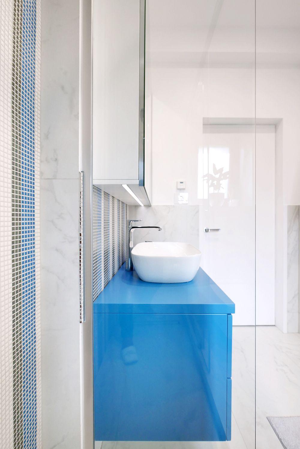 Pe peretle din zona dușului s-a mozaic Appiani comandat prin Dream Home Design, firmă de la care s-au comandat și plăcile ceramice cu aspect de marmură. Din culoarea mozaicului s-au inspirat și arhitectele când au ales nuanța mobilierului de lavoar suspendat, mobilier realizat pe comandă la Movi Design.
