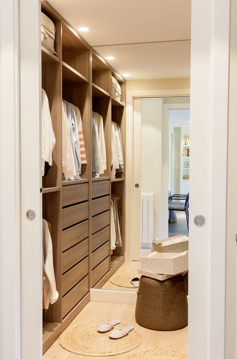 Între dormitor și baie este configurat un loc suplimentar de dressing, deci un alt spațiu de depozitare mult dorit de către proprietari. Între corpurile de mobilier situate de-o parte și alta a spațiului este montată o oglindă în care se vede o parte din zona de zi.
