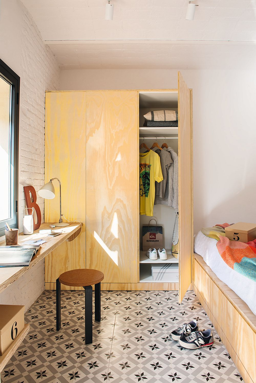 Pe lângă depozitarea de sub pat, în dormitor mai este prevăzut și un dulap, volum continuat frumos în fața ferestrei cu un loc de birou. Toată mobila este realizată dîn aceleași materiale pentru a conferi un aer unitar, luminos, cald întregii amenajări.