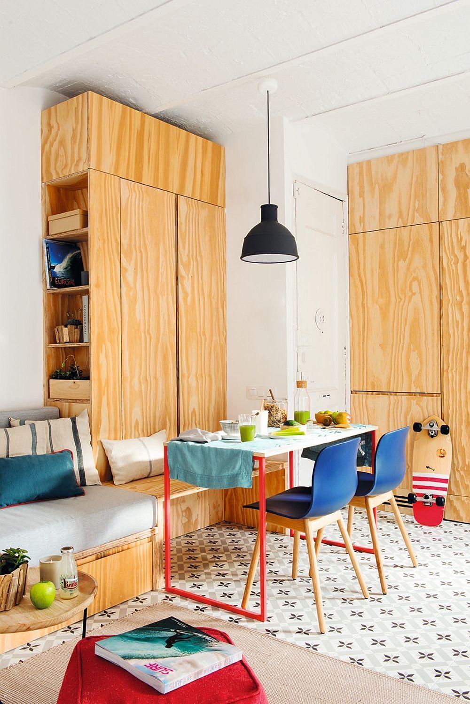 Imediat după ușa de la intrare este adaptat locul pentru frigider, iar în continuarea locului de luat masa a fost făcută pe comandă o canapea. De remarcat faptul că accentele de culoare de la nivelul micului mobilier și decorațiunilor pot colora cu efect ambianța.