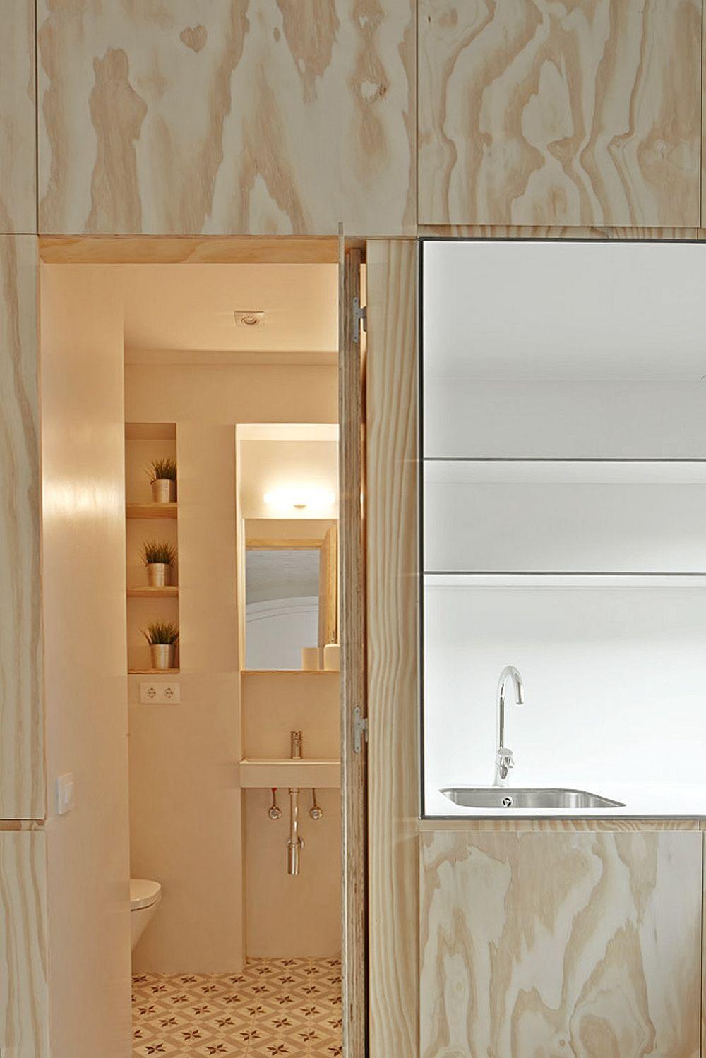 Ușa băii este gândită în continuarea mobilierului pentru bucătărie, ceea ce contează în aspectul ordonat al acestui colț de garsonieră.