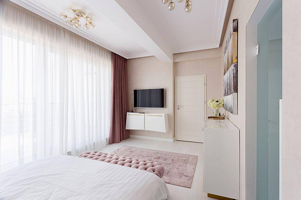 În dormitorul matrimonial este și un loc de tv, poziționat pe peretele cu ușa de acces. Albul contează mult în atmosfera camerei, alb care contrastează subtil cu restul finisajelor, obiectelor.