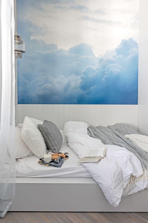Pentru a personaliza zona patului, designerul a prezăvut un fototapet care dă impresia că mai există o fereastră prin care se văd norii. Pe lângă efectul vizual contează și contrastul cromatic, respectiv abastrul în combinație cu albul, care dă impresia de prospețime. Patul este încdrat de perdele care te duc cu gândul la un colț de relaxare, mai degrabă decât la o zonă de dormit.