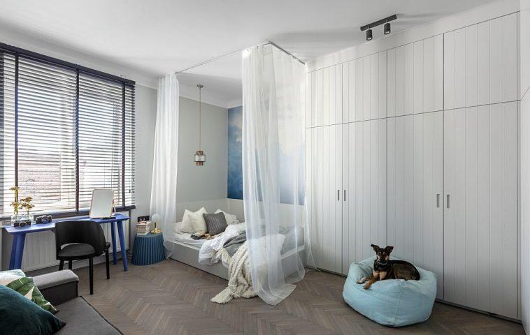 Da, pat, canapea și dressing în același spațiu, dar mai mult și loc de birou. Pentru ca zona de depozitare să nu încarce spațiul, dulapurile au fost gândite pe toată înălțimea camerei, iar fețele lor tratate cu frezări care să imite lambriurile. Alb mult pentur luminozitate, care contează foarte mult în ambianța degajată a încăperii.