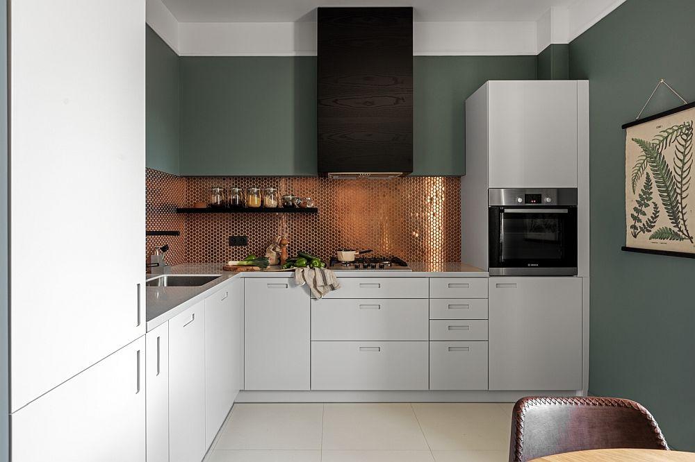 Bucătăria este mobilată cu un ansamblu realizat pe comdă, cu mânere frezate. Totul simplu în contrast de alb și negru, plus verdele închis de pe pereți, dar tușele elegante sunt date prin prezența unui mozaic metalic și a modului cum este realizat volumul paralelipipedic ce maschează hota și tubulatura de evacuare a acesteia.