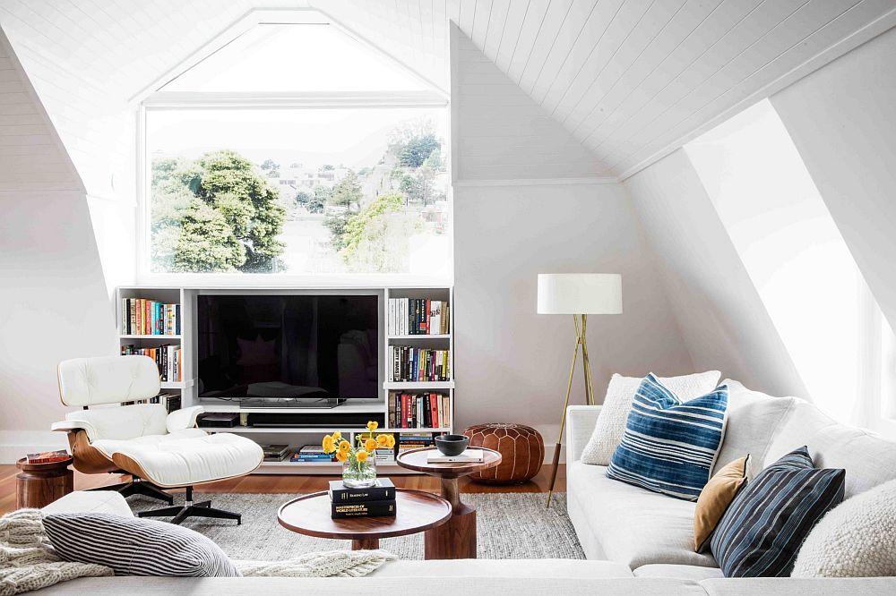 La mansardă forma ferestrei poate fi un bun prilej de a completa spațiul cu o bibliotecă în care este integrat și locul de tv. Lumina naturală este binevenită din spatele ecranului.