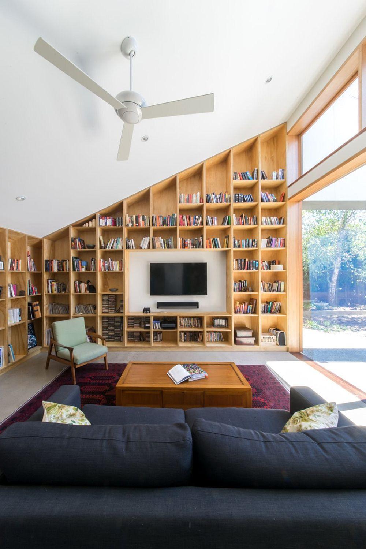 Când forma spațiului este una mai deosebită și soluțiile pentru bibliotecă pot fi inedite. Aici placarea de perete și biblioteca sunt gândite în continuarea tîmplăriei din lemn și urmînd linia dată de panta acoperișului. O soluție simplă și elegantă, care însă ne arată cât de important este și spatele rafturilor și ce impact pot avea în amenajare.