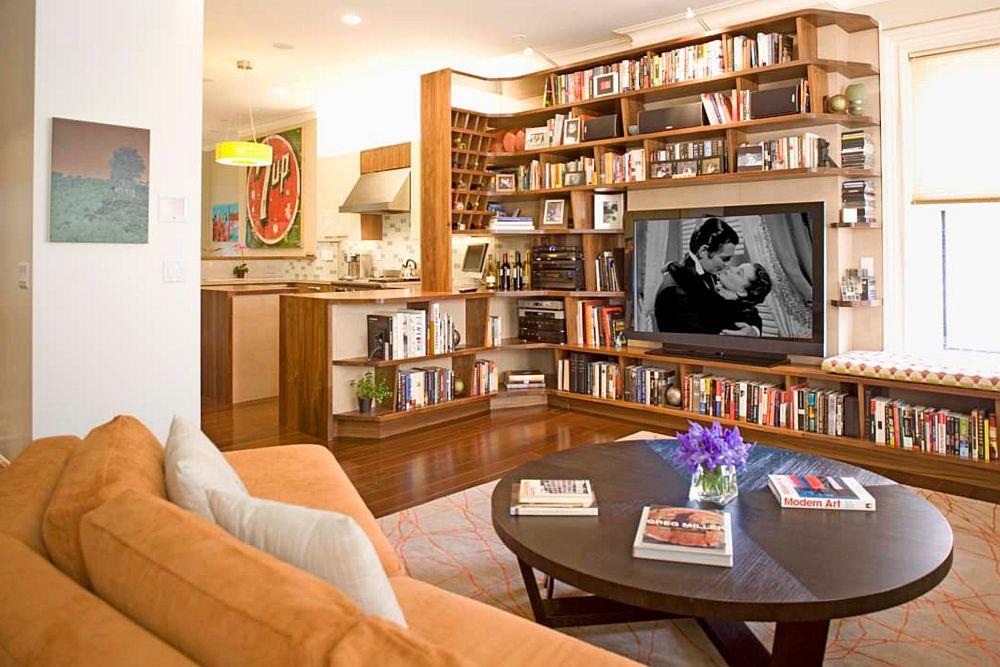 Biblioteca poate deveni și element de separare între funcțiunile unui spațiu deschis unde coexistă livingul și bucătăria, iar în ansamblul de rafturi poate fi inclus și locul pentru tv.
