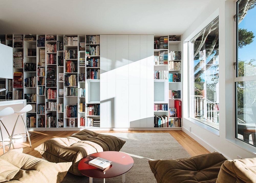 Într-un living unde biblioteca este una dominantă și unde nu se dorește ca televizorul să fie prezent ca obiect tot timpul, o ușă culisantă rezolvă două probleme: să devină o suprafață liberă care să mai estompeze din multitudinea de cărți și apoi să camufleze televizorul.