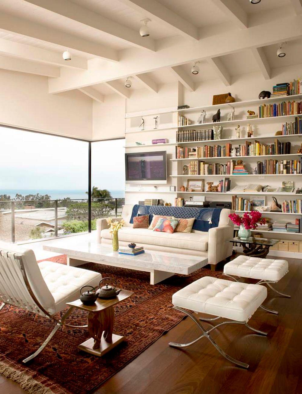 Ferestrele pot fi amplasate asimetric într-un spațiu, așa că și biblioteca poate fi gândită cu un desen asimetric. În cazul de față prezența brnelor de la nivelul tavanului, fereastra pe colț au provocat arhitecții să găsească o soluție simplă și de efect: rafturi orizontale și nu o împărțire a bibliotecii pe verticală pentru că sigur nu s-ar fi putut coordona perfect cu bîrnele din lemn. Locul de tv? Într-un capăt convenabil al bibliotecii.