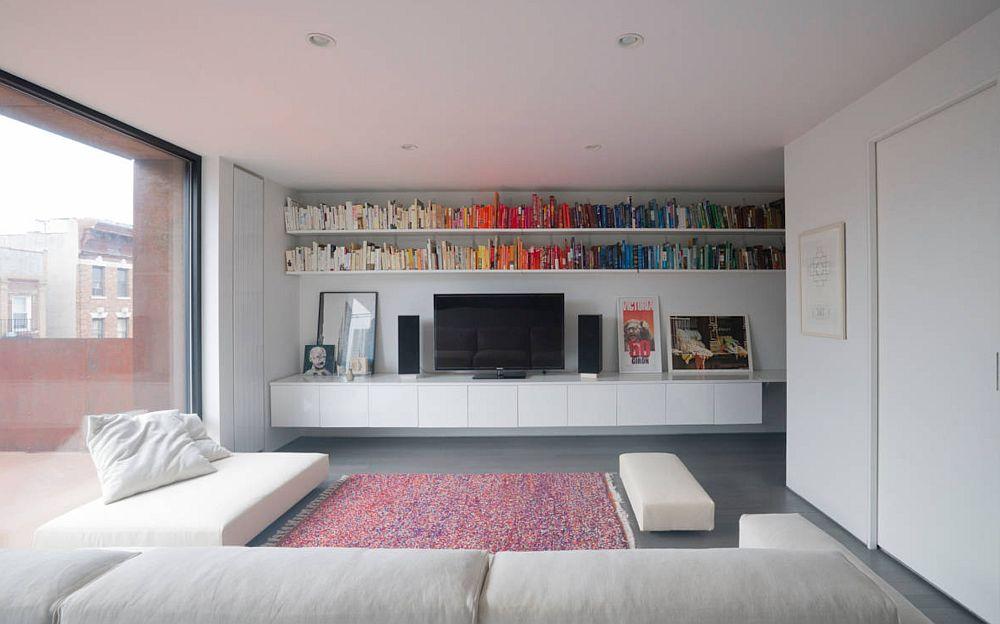 Biblioteca gândită nu ca și ansamblu de mobilă, ci ca o grupare de rafturi deasupra comodei tv.