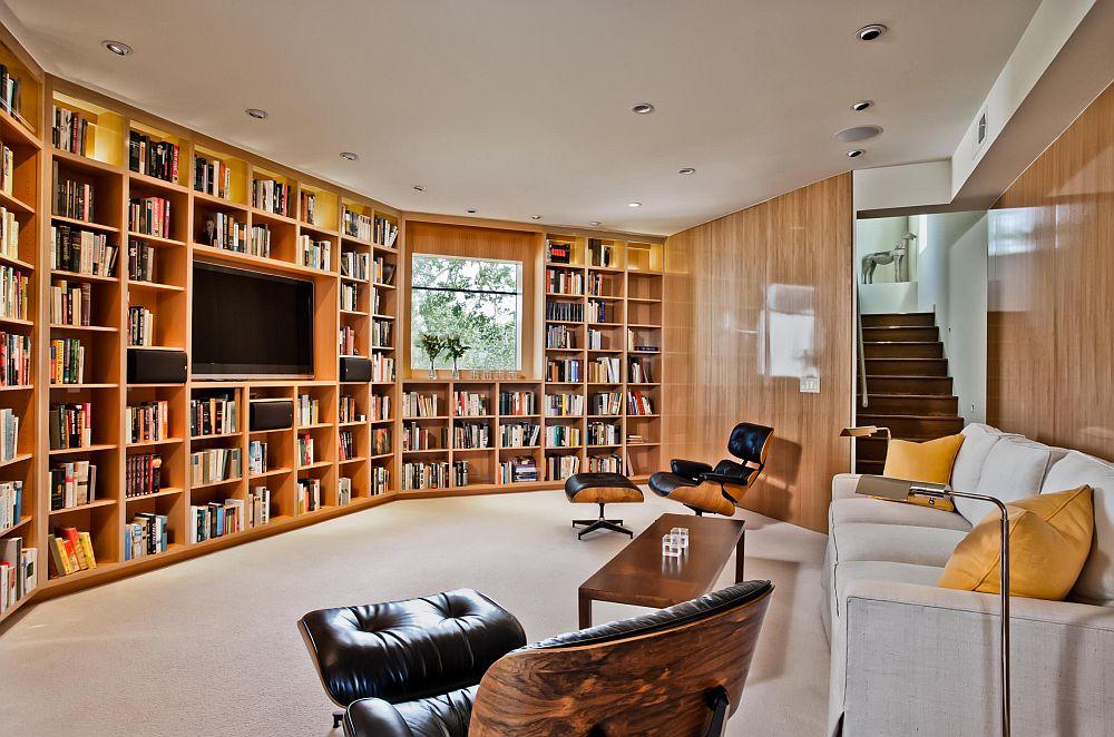 Forma atipică a spațiului și o fereastră care pare să incomodeze. Soluția? Tot peretele tratat ca o bibliotecă, unde atât televizorul, cât și fereastra sunt integrate, astfel încât ambele să fie situate ăn partea de jos deasupra aceleași linii.