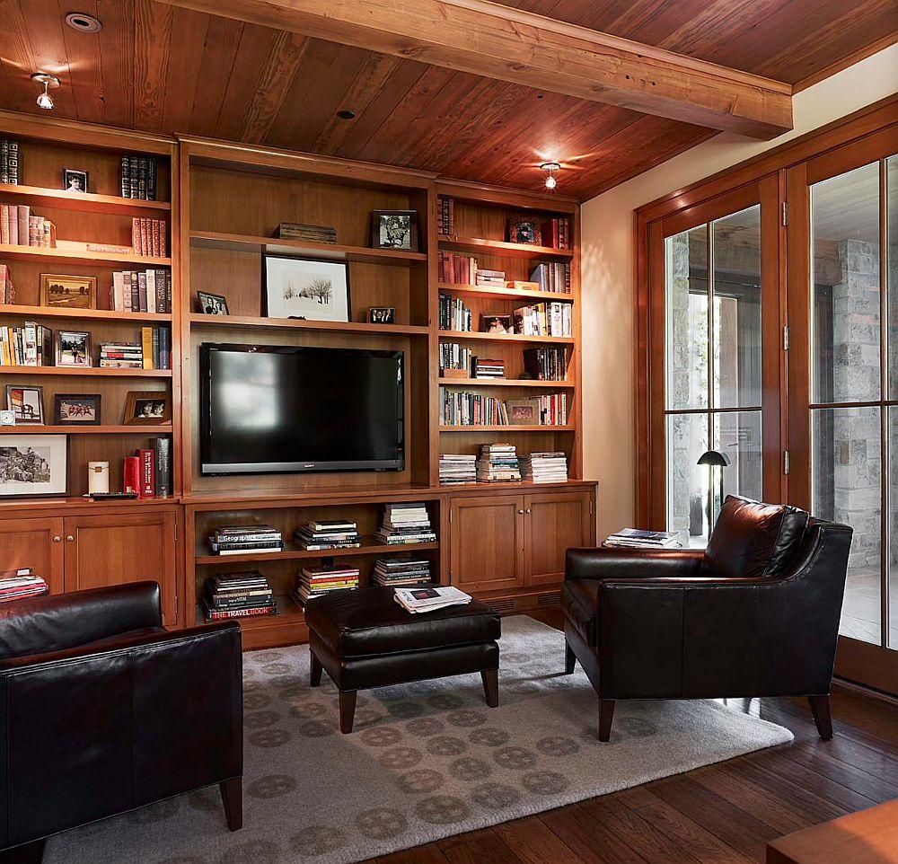 Simetria contează pentru o amenajare clasică, rustică sau tradițională. Ce faci ca televizroul să nu apară prea evident într-o bibliotecă din lemn masiv? Poți avea alte piese mari și negre în încăpere, cum sunt aici fotoliile.