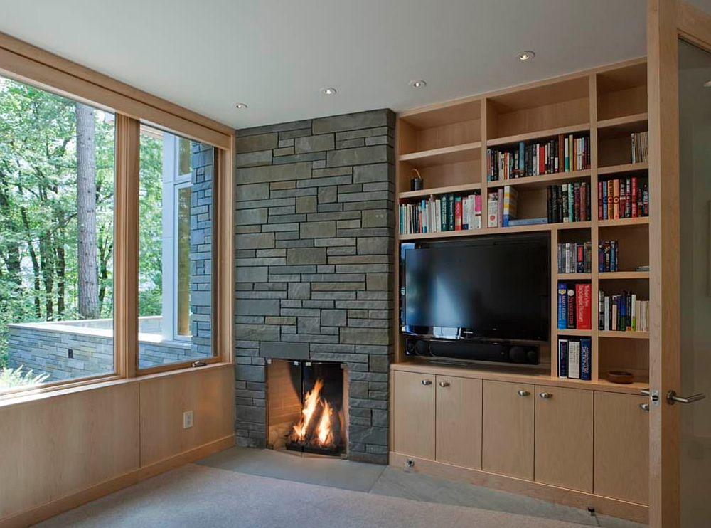 Vrei bibliotecă, vrei șemineu, dar vrei și un ditamai televizorul? Atunci musai să scoți unul dintre aceste elemente în evidență. În cazul de față placarea șemineului s-a făcut cu o piatră mai închisă la culoare pentru a căpăta greutate, iar în dreptul focarului partea de bibliotecă este închisă pentru ca atenția să fie asupra gurii șemineului și nu asupra cărților. Televizorul deasupra liniei șemineului și înconjurat de rafturi entru cărți. Deci da, se poate rezolva.